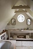 Uriges, kleines Badezimmer mit Rundfenster im Dachgeschoss eines Bauernhauses