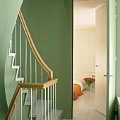 Blick vom grünen Treppenhaus in ein dezent dekoriertes Schlafzimmer