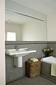 Ein mosaikbefliestes Badezimmer mit Spiegelwand