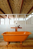 Die alte Clawfoot Badewanne wird durch ihren orangefarbenen Anstrich zum knalligen Blickfang