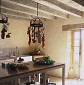 Einfache Kücheneinrichtung und hängende Hakenaufbewahrung in einem urigen Bauernhaus