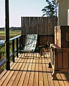 Ein filigraner Liegestuhl und ein antiker Holzschrank auf der Veranda