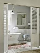 Blick durch die Jalousieschiebetür in ein romantisches Badezimmer mit Holzboden und alter Badewanne