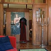 Stehkandelaber und Schaufensterpuppe mit rotem Abendkleid in einem historischen Wohnraum