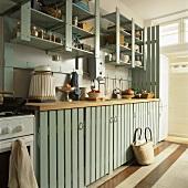 Eine einfache Küchenzeile aus Holz mit Hängeregalen und Steinboden