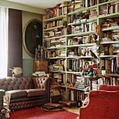 Schönes Chesterfieldsofa neben einem gut gefüllten, raumhohen Bücherregal