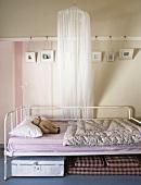 Metallbett im Shabby Chic und ein Betthimmel vor der gestreiften, dekorierten Wand eines Kinderzimmers