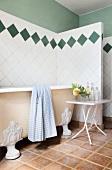 Antike, freistehende Badewanne und ein weisser Klapptisch vor der rautengefliesten Wand des Badezimmers