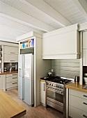 Holzbalkendecke und Zierleisten verleihen der klassisch modernen Einbauküche einen dezenten Landhaustouch