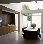 Minimalistische Küche mit Esstisch vor einer verglasten Terrassenfront in moderner Architektur
