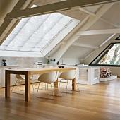 Designerstühle und Esstisch vor dem großen Fenster des ausgebauten Dachraums