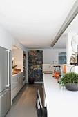 Schlauchörmige Küchenzeile mit minimalistischen Fronten und Edelstahlkühlschrank