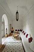 Weisser Wohnraum im marokkanischen Stil mit langer Polsterbank und vielen Teppichen