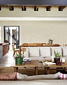 Rustikale Couchtische und helle Sofas vor einem großen Esstisch mit Biedermeierstühlen in einem offenen Wohnraum mit Holzbalkendecke