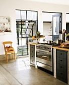 Kleine Küchentheke mit Edelstahlherd vor Terrassentür und Fabrikfenster