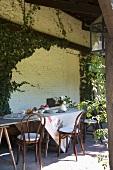 Gedeckter Tisch und Thonetstühle auf einer überdachten Terrasse