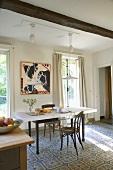 Thonetstuhl am schwarzweissen Küchentisch einer schönen Landhausküche mit Fliesenmuster und Deckenbalken