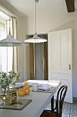 Zwei verschiedene, klassische Küchenleuchten über einem gedeckten Frühstückstisch mit Thonetstuhl