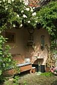 Gemütlicher, reich begrünter Aussenbereich eines Wohnhauses mit antiker Holzbank und Beistelltisch