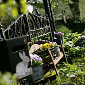 Garden seat in front of garden gate with pansies in containers