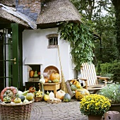 Pumpkins and autumn flowers outside thatched house