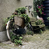 Old bicycle with plants in baskets (garden ornament)