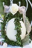 Easter decoration: ostrich egg with box, rose and bow