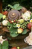Sommerdeko: Rostvase mit Schneckenhaus, Beeren und Rosen