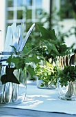 Garden party: cutlery in glasses decorated with greenery