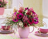 Poppy anemones, hyacinths, broom, asparagus fern in a jug