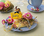 Easter place-setting with primulas, hay, Easter egg & place card