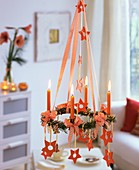 Hanging Advent wreath with fir, candles, stars, gingerbread