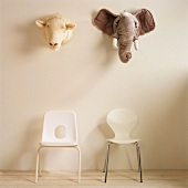 A sheep's head and an elephant's head above two chairs