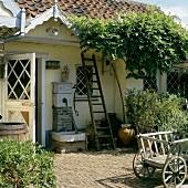 Eingewachsenes, altes Haus mit Wasserbrunnen neben der Haustüre und einem davorstehenden, antiken Holzwagen
