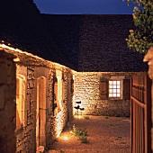 Beleuchtetes, rustikales Landhaus in der Nacht