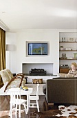 Wohnzimmer mit Fernsehgerät über dem offenen Kamin und Wandnische als Regalwand; im Vordergrund ein spielendes Kind
