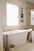 Freistehende, moderne Badewanne in Badezimmer mit Marmorfliesen an der Wand und einem weissen Holzdielenboden