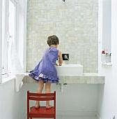Kind auf einem Stuhl stehend beim Händewaschen