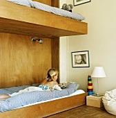 Lesendes Mädchen in Kinderzimmer mit Stockbett