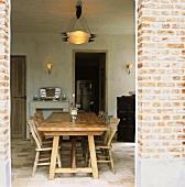 Langer, massiver Esstisch aus Holz mit Stühlen in rustikal verputztem Raum