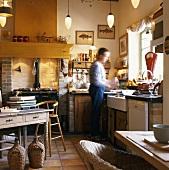 Landhausküche mit antikem Küchenofen und kochendem Mann