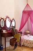 Mädchen sitzt an Schminktisch in Kinderzimmer mit rosafarbenem Himmelbett