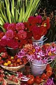 Pinkfarbene Blumen in Eimern mit Chilischoten und Tomaten