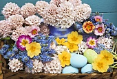 Spring flowers and Easter eggs in a basket