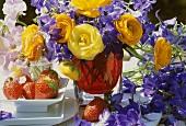 Summer arrangement of ranunculus & delphiniums, strawberries