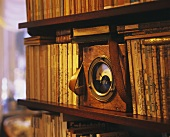 Shelf of antique books with old ammeter