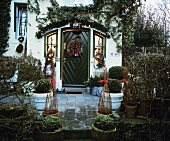 Box trees in front of decorated house door
