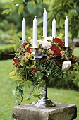 Candlestick decorated with flowers on pedestal out of doors