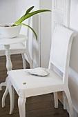 Weisser Stuhl mit Dekoherz neben Beistelltisch mit Amarillis in weisser Porzellanschale