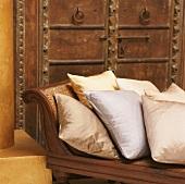 Ausschnitt einer Chaiselongue mit verschiedenen Dekokissen aus Seide